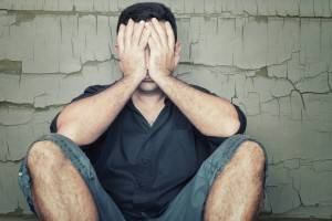 bigstock-Depressed-young-man-sitting-on-62516594-300x200